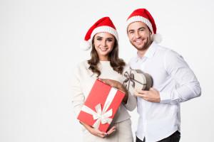 Zwei Personen mit Weihnachtsmütze und Geschenk
